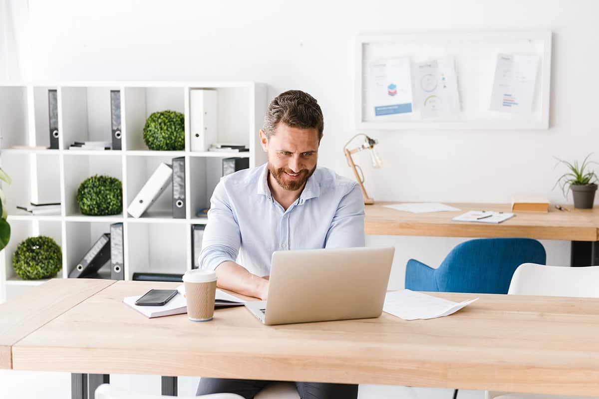 happy bearded man sitting in office working 4HVP863